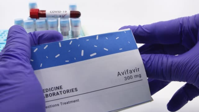 Doctor showing box of medicine for covid-19 treatment.Concept of Avifavir medicine with blood tests tubes on the background.Cure for coronavirus,COVID-19 treatment. Dubai-UAE-Circa 2020:Doctor showing box of medicine for covid-19 treatment.Concept of Avifavir medicine with blood tests tubes on the background.Cure for coronavirus,COVID-19 treatment. remdesivir stock videos & royalty-free footage
