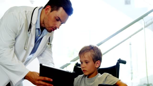 läkare visar digitala tablett inaktivera pojke - digital reading child bildbanksvideor och videomaterial från bakom kulisserna