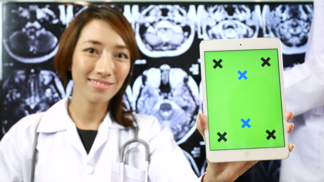 Doctor showing green screen of Digital tablet on Brain X-ray image bachground, Chroma Key video