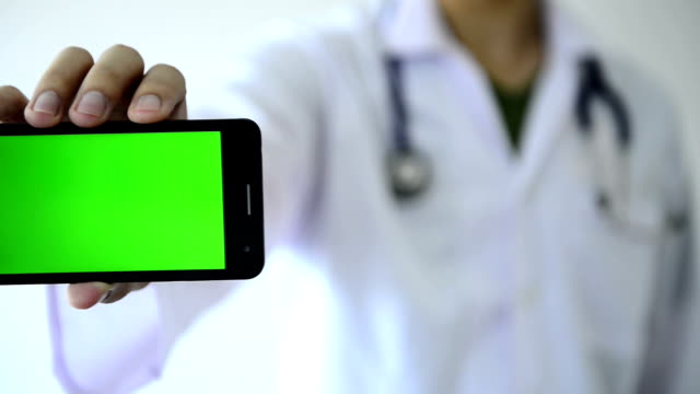 Doctor showing green screen of smartphone video