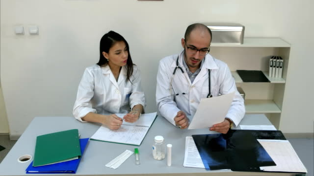 Doctor showing his female assistant how to read cardiogram while she making notes video
