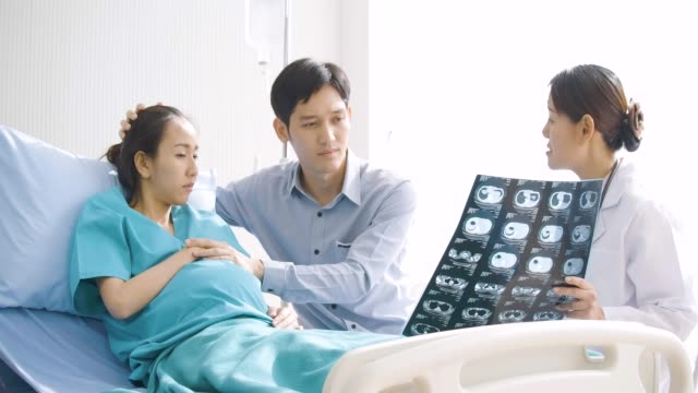 Doctor showing X-ray scan results to pregnant woman and her husband with serious emotion. People with healthcare and medical concept. video