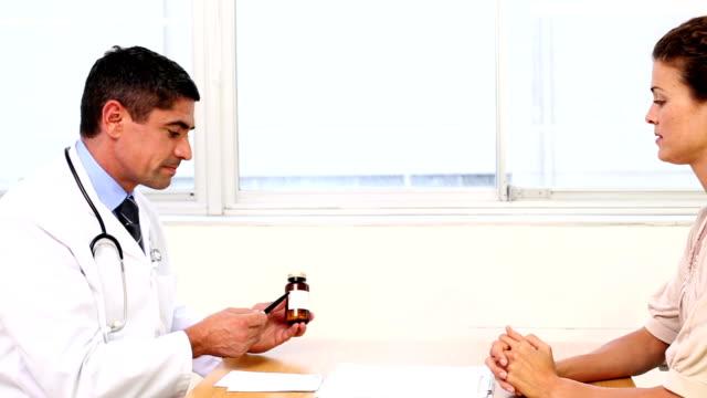vidéos et rushes de médecin parlant avec son patient malade au bureau sur ordonnance médicale - pots de bureau