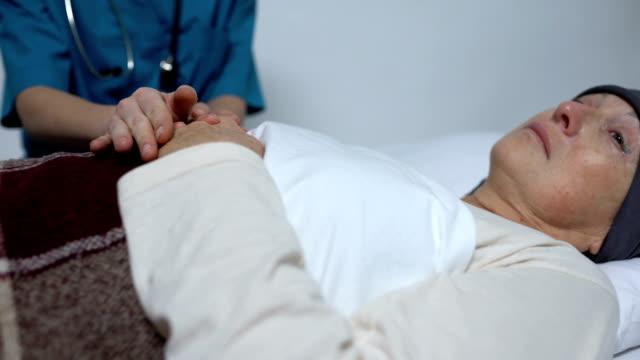 医師は癌の最後の段階で女性をサポートし、彼女の手をなでる、ホスピス ビデオ