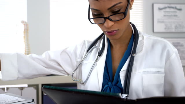 Doctor taking notes and working in office video