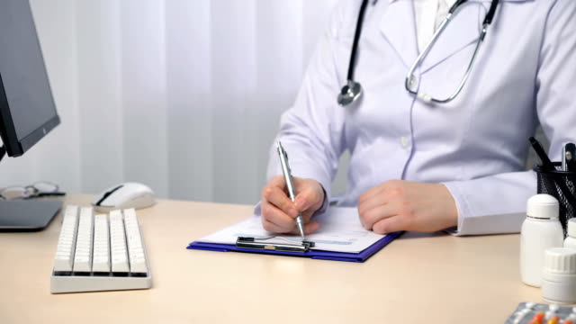 Doctor taking notes, filling out medical papers, keeping records in their office