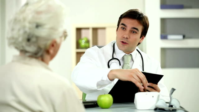 Doctor taking pillsand giving a apple to patient. video