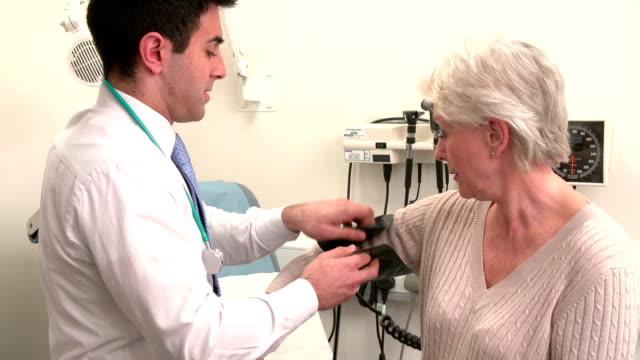 Doctor Taking Senior Female Patient's Blood Pressure video
