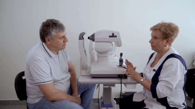 Doctor talk with patient after checking his eyesight on the modern equipment Doctor talks with patient after the procedure of checking eyesight. The man look on the doctor sitting near optical modern equipment. eye exam stock videos & royalty-free footage