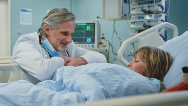 Doctor talking and giving high-five to boy in ward