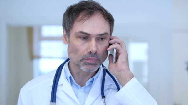 Doctor Talking on Phone, Attending Phone Call video