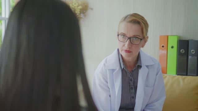 doctor talking to female patient,dolly shot - brązowe włosy filmów i materiałów b-roll