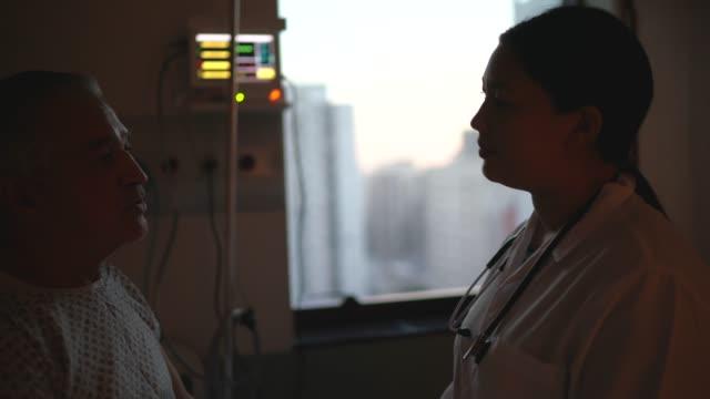 arzt im gespräch mit patient im krankenhauszimmer - geduld stock-videos und b-roll-filmmaterial