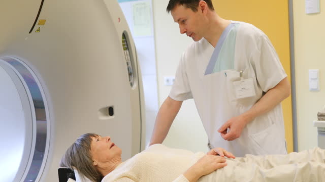 Doctor talking to patient lying on CAT scanner video