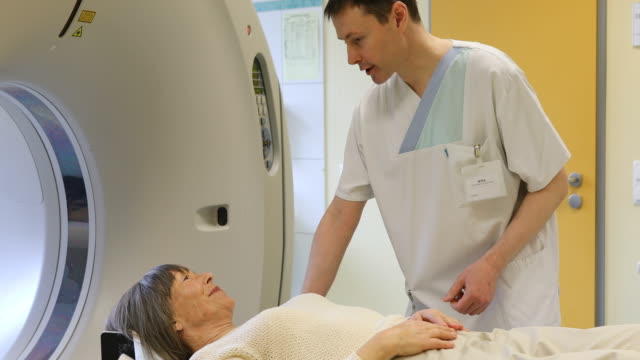 Doctor talking to patient lying on MRI scanner video