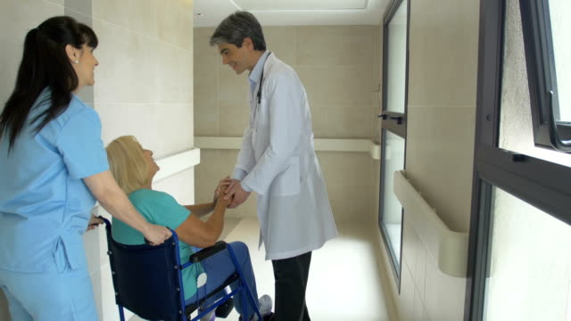 Doctor talking to patient on wheelchair and nurse video