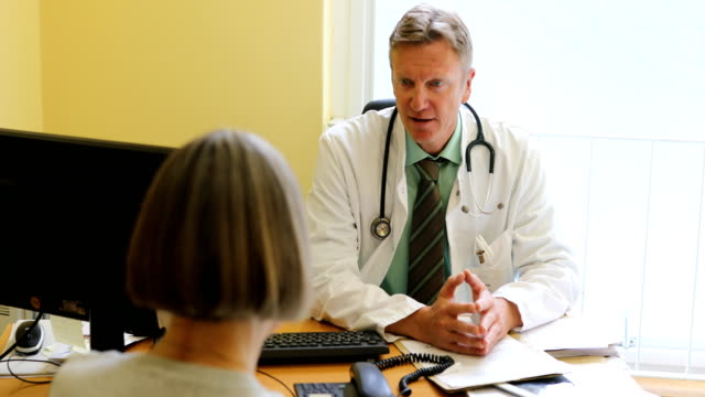 Doctor talking to patient while sitting at clinic Lockdown shot of confident doctor talking to patient. Male medical professional is consoling woman. They are sitting at desk in clinic general practitioner stock videos & royalty-free footage