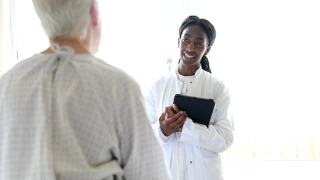 doctor talking to senior female patient in hospital bed - liczba osób filmów i materiałów b-roll