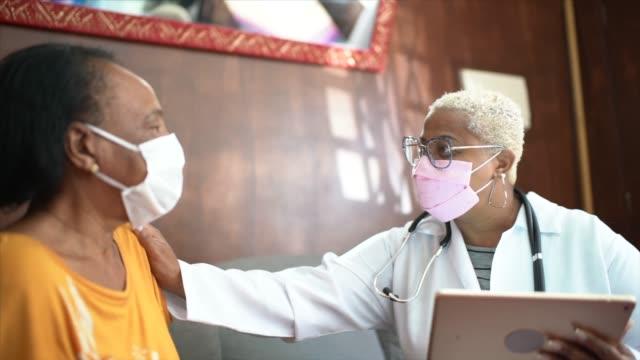 doktor bir ev ziyareti sırasında kıdemli kadın hasta ile konuşurken - ziyaret stok videoları ve detay görüntü çekimi