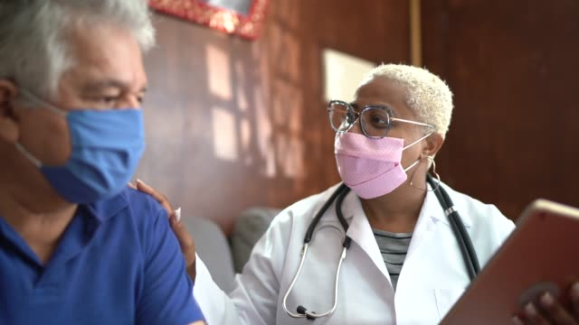 Doctor talking to senior male patient while being in a home visit