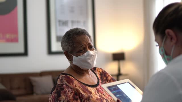 läkare pratar med äldre kvinna patient på läkarbesök i sitt hem - med ansiktsmask - omsorg bildbanksvideor och videomaterial från bakom kulisserna