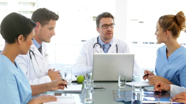 Doctor talking with his staff during a meeting video
