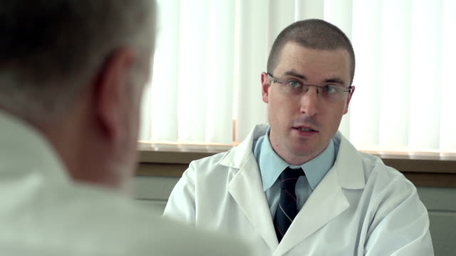 Doctor talking with patient in his office video