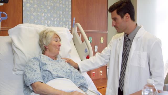 arzt spricht mit senior patienten im krankenhaus bett/videoformat r3d - männliches tier stock-videos und b-roll-filmmaterial
