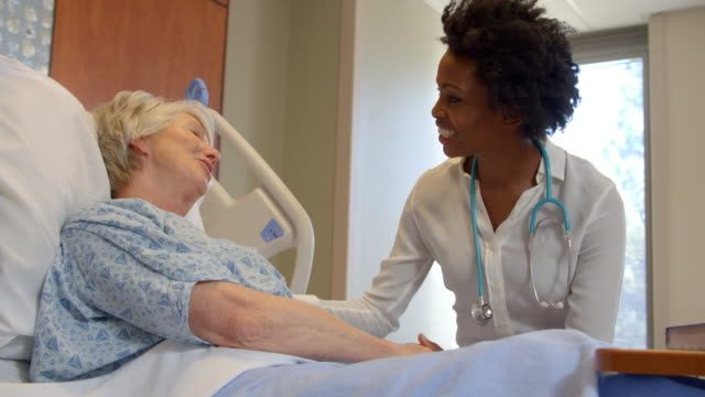 Doctor Talks To Senior Patient In Hospital Bed Shot On R3D