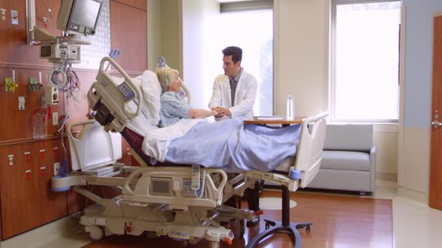 arzt spricht mit senior patienten im krankenhaus bett/videoformat r3d - krankenstation stock-videos und b-roll-filmmaterial