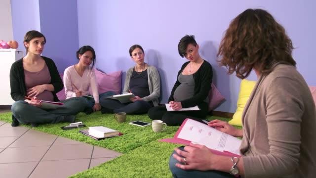 カウンセラー助産師医師によるクラスを教える妊娠中の女性 ビデオ