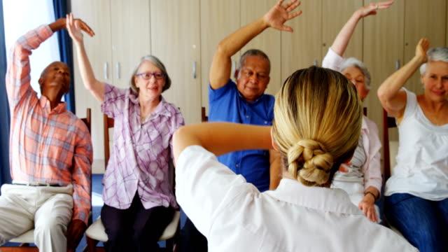 Doctor teaching exercise to senior people 4k video