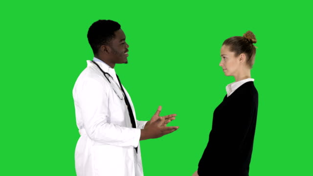 doctor telling good news to a patient on a green screen, chroma key - affidabilità video stock e b–roll