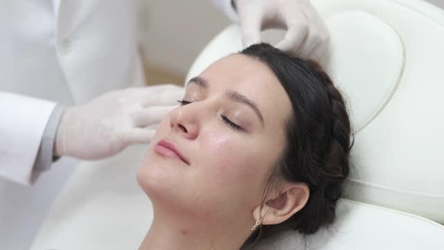 lekarz trycholog badający kobiecą skórę głowy włosów na wyprysk, zapalenie skóry, łuszczycę, wypadanie włosów, łupież lub suchy problem skóry głowy - kosmetyczka praca w salonie piękności filmów i materiałów b-roll
