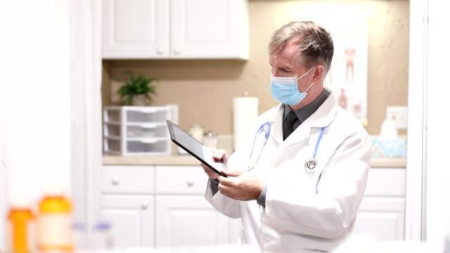 COVID-19: Doctor uses digital tablet, wears mask. video
