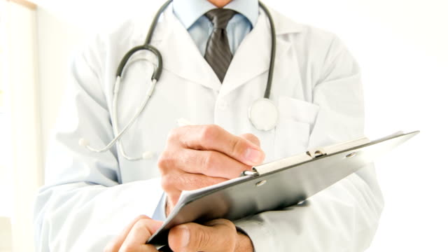 Doctor using clipboard to write video