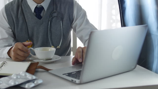 Doctor using Labtop and Drink Coffee video