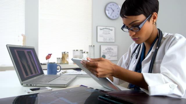 vídeos y material grabado en eventos de stock de médico usando ordenador portátil y una tableta de revisión de rayos x - brazo humano