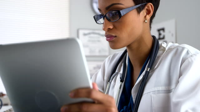 Doctor using tablet pc and laptop computer video