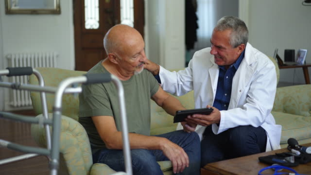 Doctor using tablet while talking with senior male patient