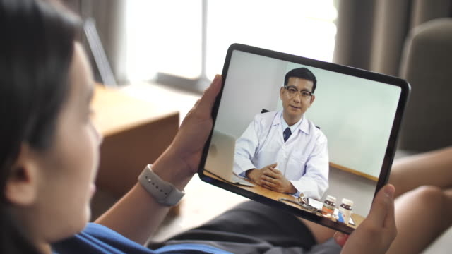 Doctor video conference on Digital tablet to patient woman at her home