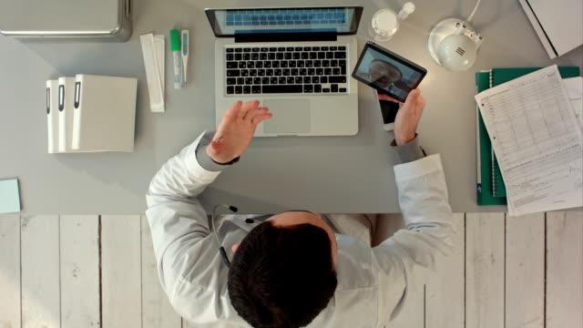Doctor Videochatting met senior collega op de Tablet. Bovenaanzicht video