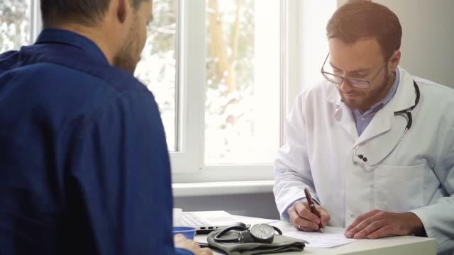 医師訪問 - 患者のための処方箋を書く - 処方箋点の映像素材/bロール