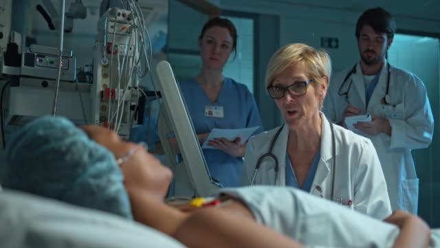 ds läkare besöker hennes kvinnliga patienten på iva efter operation - sjukvårdsutrustning bildbanksvideor och videomaterial från bakom kulisserna