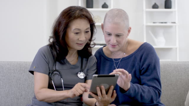 Doctor visits cancer patient at her home A Korean doctor is making a home visit to see a patient. The patient is a caucasian woman with cancer. The cancer patient has a shaved head because chemotherapy treatment has caused hair loss. The doctor is showing the patient test results on a digital tablet. The two women are smiling at one another. test results stock videos & royalty-free footage