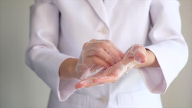 läkare tvätta händerna med skumtvålför att rengöra virus, bakterier och bakterier. vit enhetlig bakgrund. på nära håll. tvätt ning är sättet att förhindra spridning covid19. - washing hands bildbanksvideor och videomaterial från bakom kulisserna