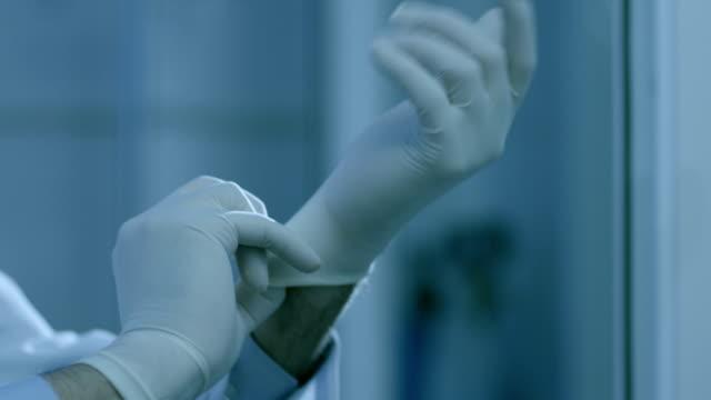 vídeos y material grabado en eventos de stock de doctor con guante en el hospital. guantes médicos. trabajador de asistencia sanitaria a los guantes médicos. - guante quirúrgico