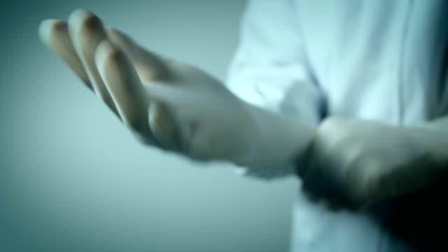 vídeos y material grabado en eventos de stock de médico que usa guantes médicos - guante quirúrgico