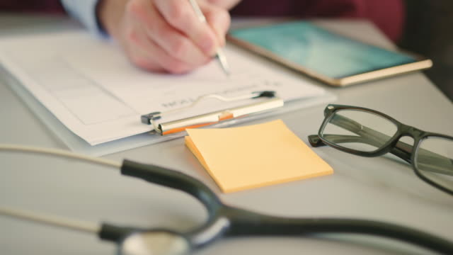 doctor with digital tablet filling rx prescription at desk 4k - prescrizione medica video stock e b–roll