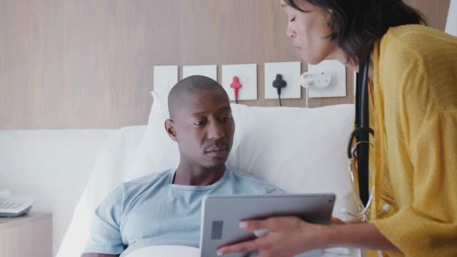 врач с цифровым планшетом посещения и говорить с пациентом мужского пола в больничной койке - пациент стоковые видео и кадры b-roll